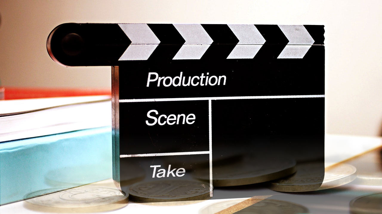 Film clapperboard and gold coins